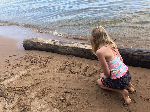 child writing in sand
