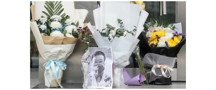 A photo of the late ophthalmologist Li Wenliang is seen with flower bouquets at the Houhu Branch of Wuhan Central Hospital in Wuhan in China's central Hubei province, Feb. 7, 2020.