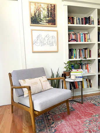 Image of Ashley Batistick's office where she sees couples and individuals for therapy. Image includes a chair, bookshelf with books, and a side table where potted plants fill the space. The room is warm and inviting.