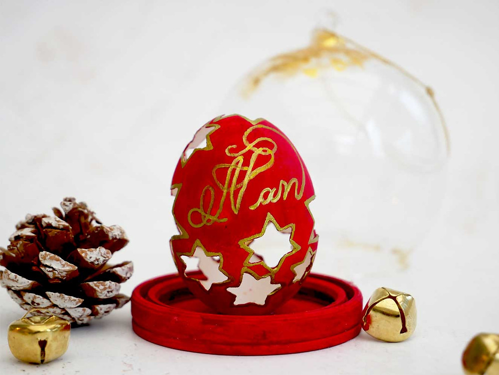 christmas bauble in a scarlet red and gold colour carved on a chicken eggshell, sealed in a glass dome