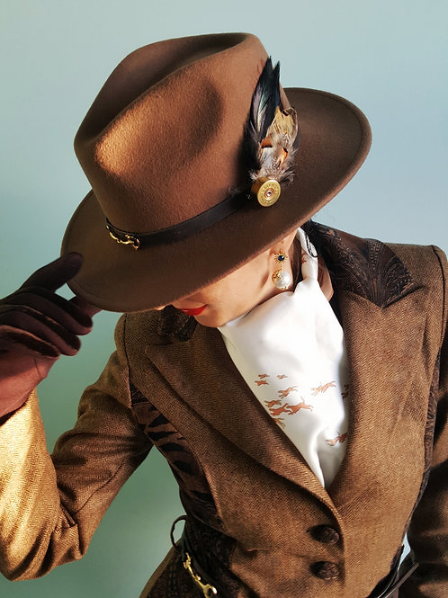 Brown snaffle bit trilby with shotgun cartridge and real feather Brooch