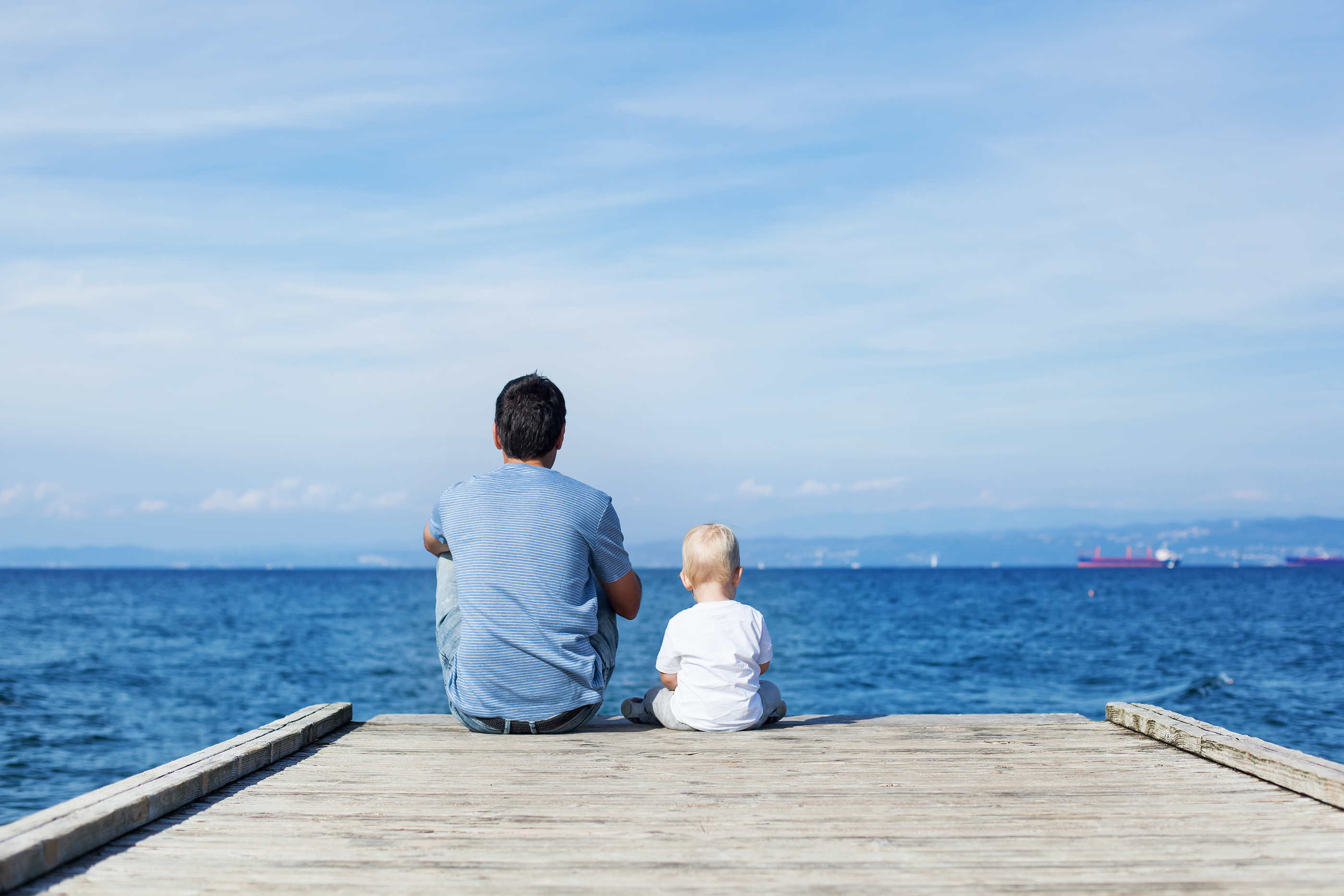Father With Son Sitting On The Sea Pier.