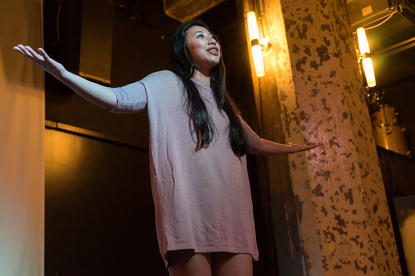 Dena Igusti, an Asian woman, performs poetry with her arms outstretched in In Full Color 2017.