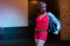 A Hispanic woman wearing red, white and blue 70's clothing dances.