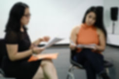 Two Asian women sit in a studio looking over a script.