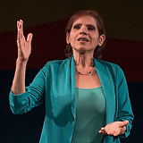 Susan Justiniano, a Hispanic/Latinx woman, with short red hair, seen performing poetry