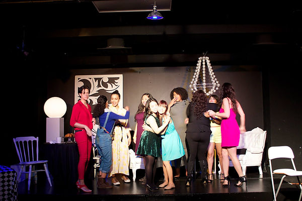 An ethnically diverse group of women smile and hug each other on stage. They are wearing clothing in different colors which contrast strongly with the set on stage, which is mostly black and white and emulates a dining room and living room.