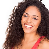 A smiling Afro Latinx woman wearing red. She has big, curly hair