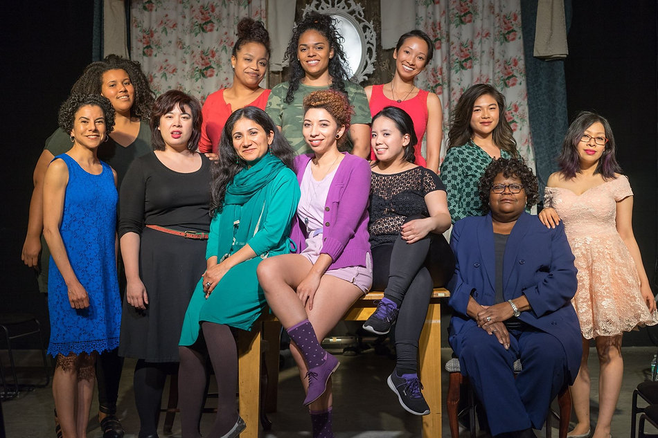 A diverse group of women pose together, smiling. Behind them are items suggesting a hyperfeminine home including a white ornate mirror and floral drapes.