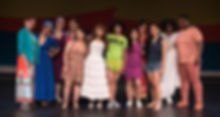 A diverse group of woman stand together and smile. They are wearing vibrant clothes. Behind them are colorful swathes of fabric -- yellow, orange and blue -- lining the wall.