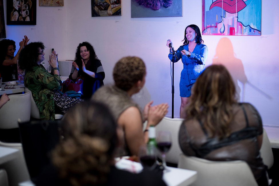 An Asian/Hispanic woman in blue holds a microphone. A diverse audience of women claps.