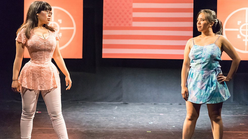 Liliane Wolf, a Hispanic/Latinx woman dressed in pink, and Summer Dawn Reyes, an Asian/Hispanic woman dressed in blue, look across the stage at each other intensely. In the background, you see pink monochrome backdrops of the female symbol in crosshairs and the American flag.