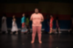 Rukiya Bluford, a Black woman wearing coral, stands centerstage, performing a poem while a diverse group of women, the cast of In Full Color 2019, crosses the stage behind her.