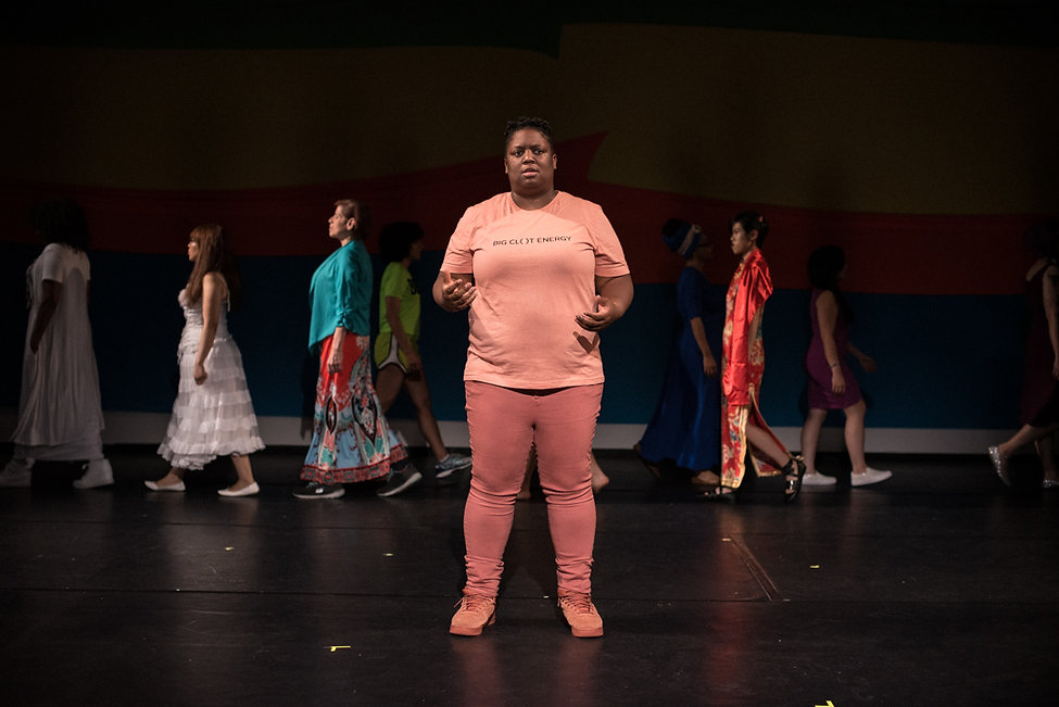 A Black woman wearing coral performs centerstage while a diverse group of women walk behind her