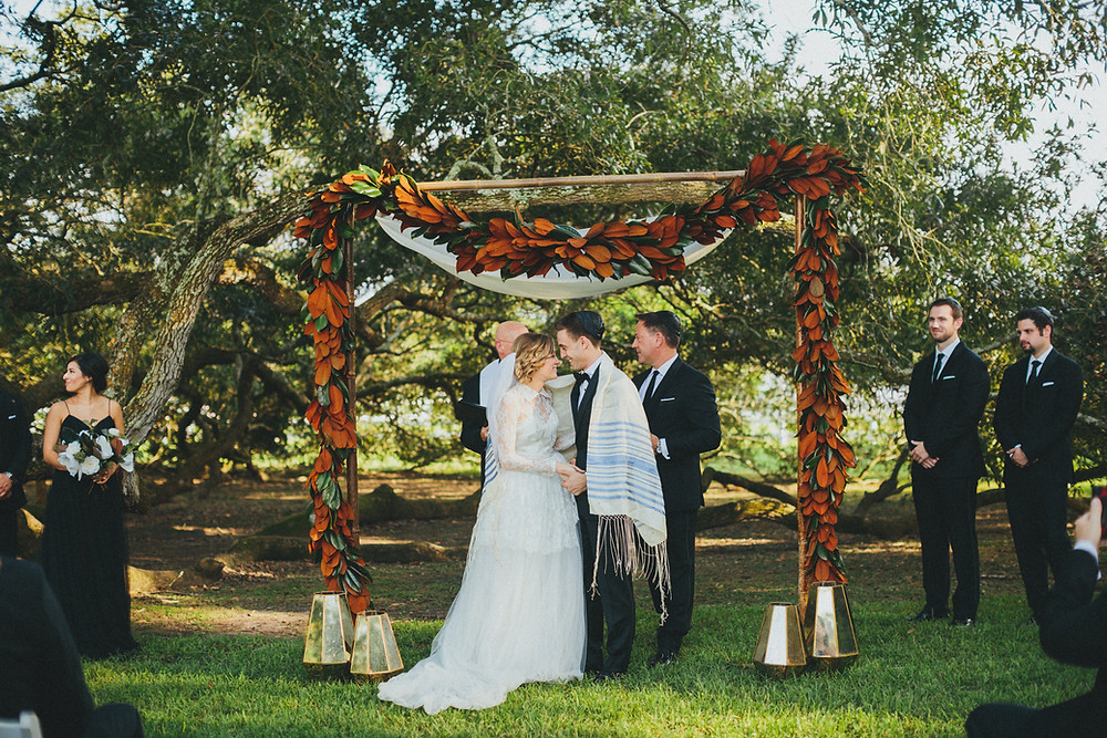 Kat & Louie's custom chuppah was created to use the lazy tree as part of the 4 posts. A little draping and our hexagon lanterns combined with the beautiful magnolia leaf garland created a romantic setting under a 250 year old oak tree.
