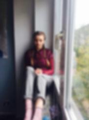 Jolie Sharon, Gründerin des veganen Foodblogs delirious life, wie sie vor einem Fenster sitzt.