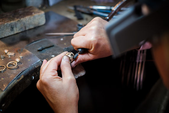 Jeweler polishes a gold ring on an old w