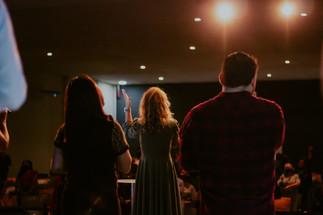 Louvor no culto com mulher levantando a mão