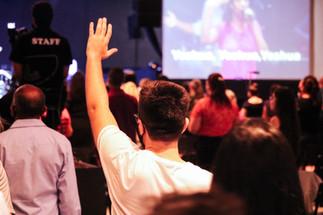 Homem levantando a mão no culto