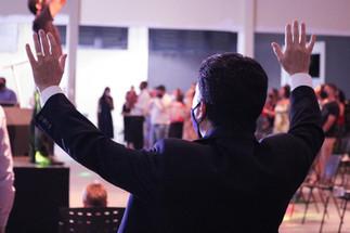 Homem levantando a mão adorando de terno