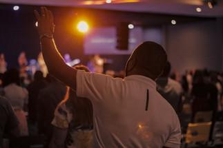 Homem levantando a mão na igreja com luz de fundo