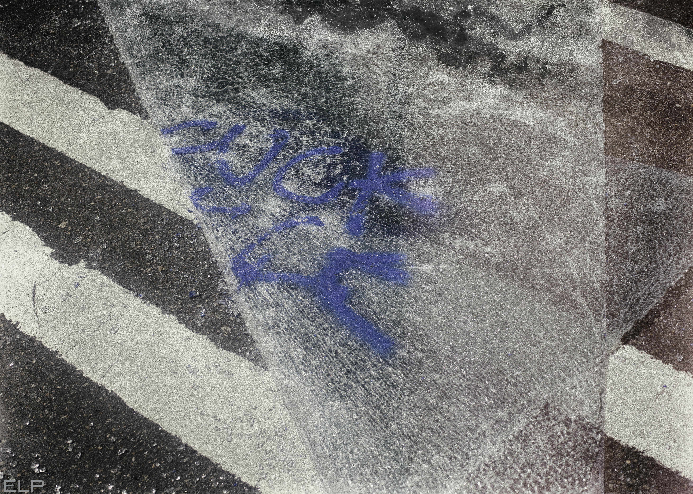 """""""Fuck ICE"""" written on broken glass shard"""