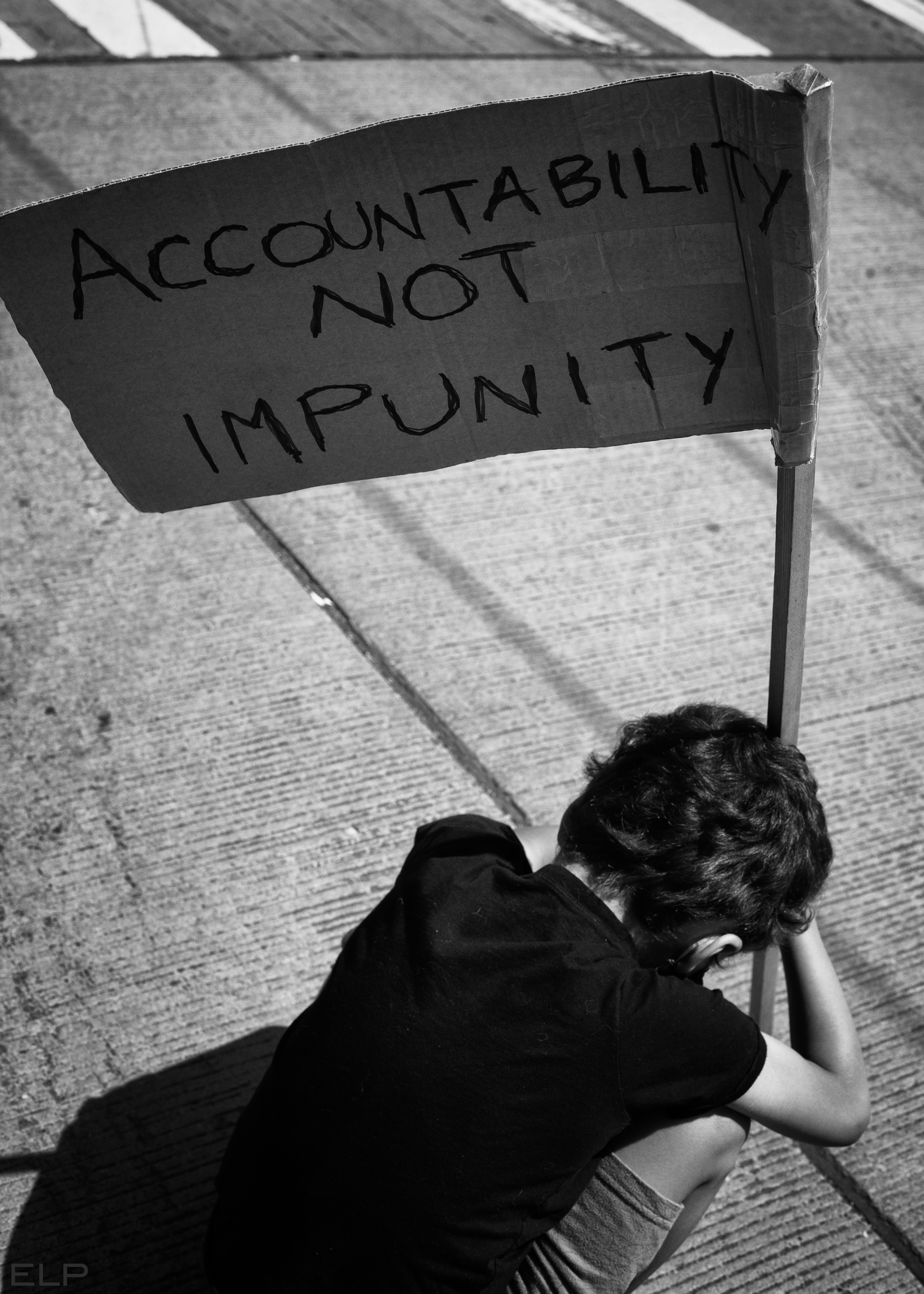 Fourth of Youly event child holding sign saying accountability not impunity