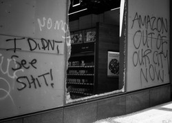 """Broken Amazon Go window with spray painted text """"I didn't see shit"""""""