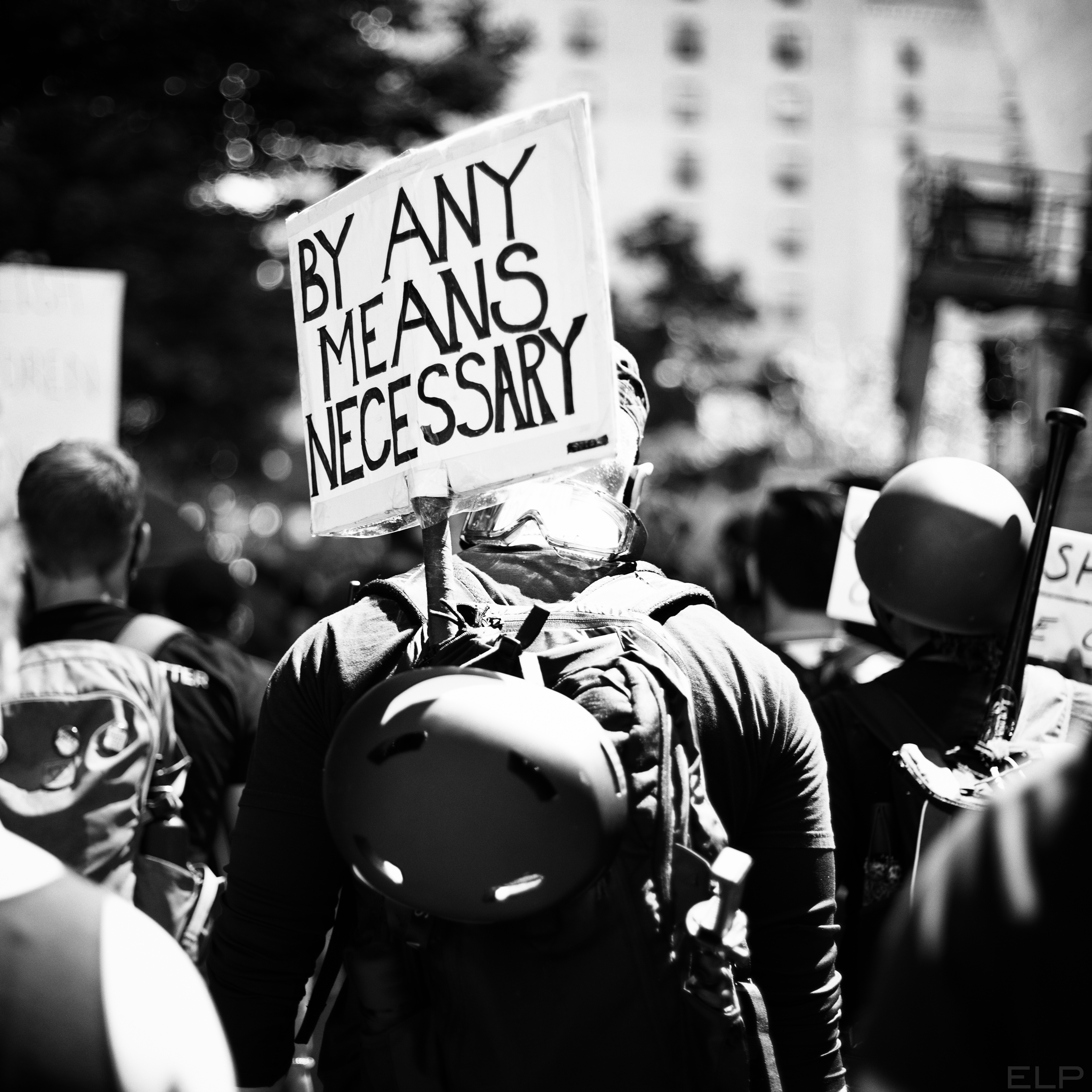 """Protester with """"by any means necessary"""" sign"""