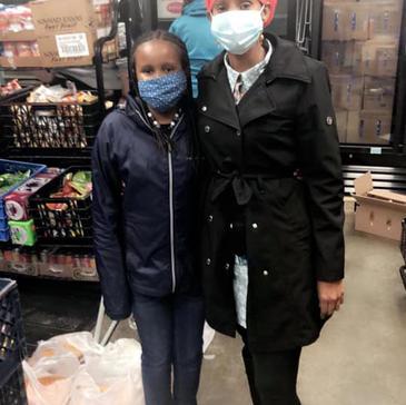 Shukri and daughter volunteer at local food bank.