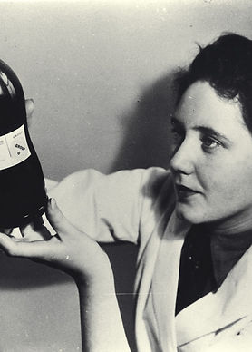A black a white photo. On the right is a woman with short dark hair in a lab coat. She is holding up and looking up a large glass bottle filled with a dark substance.