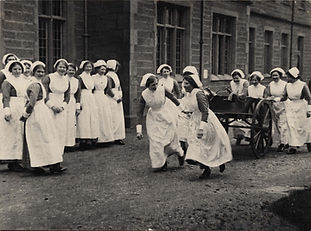A black and white photo showing a large group of nurses outdoors. Most of them are smiling or laughing. Three are pulling a cart with firefighting equipment inside, with more nurses helping by pushing from the back.