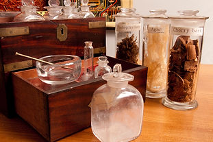 """A small wooden box sits open, with small glass jars and vials sat around it. Behind are three glass jar filled with natural objects. They are labelled: """"Podophyllum"""", """"Agar"""", and """"Cherry bark""""."""