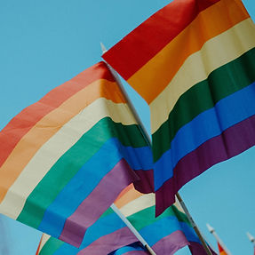 A photo of a pair of rainbow pride flags crossed and flying in a blue sky.