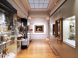 A museum space with paintings, busts and glass cabinets. The view is drawn to an oil painting at the back, which shows a man in tetanus. He is lying tense on the ground, back arched and in pain.