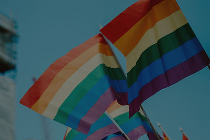 Two rainbow pride flags crossed and flying in a blue sky