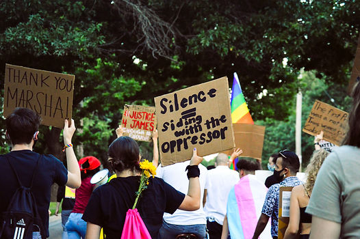 """A photo showing the back of people's heads at a protest or pride march. There are trans pride and rainbow flags in view. The person who is centred is holding up a cardboard sign that says """"Silence = siding with the oppresor"""""""
