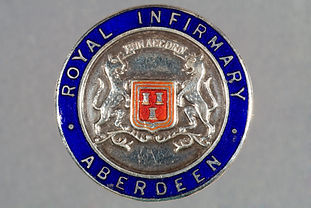 A blue and silver medal showing the coat of arms for the Royal Infirmary of Aberdeen.