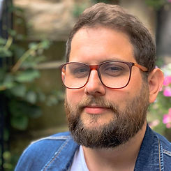 A portrait of a man with glasses. He has short, light brown hair and a long light brown beard, and is wearing a denim jacket. He has a small smile.