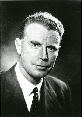 A black and white bust portrait photo of a man with short hair wearing a suit, looking directly into the camera.