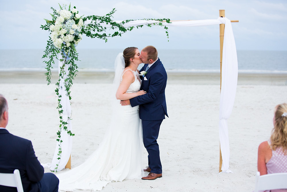bride and groom kissing under arch during beach ceremony