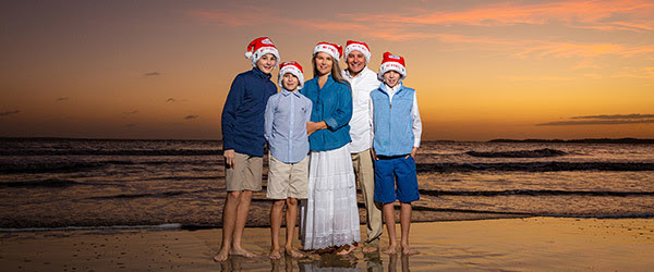 family in santa hats on beach at sunset