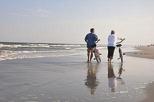 couple walking bikes on beach