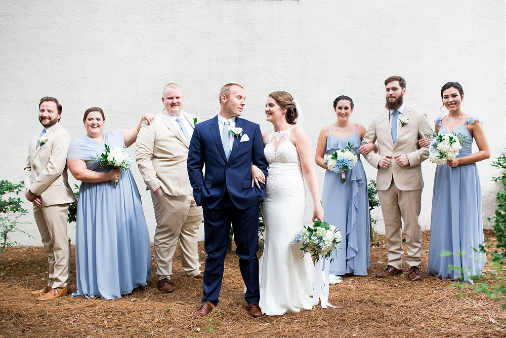 bride and groom and bridal party posing outside