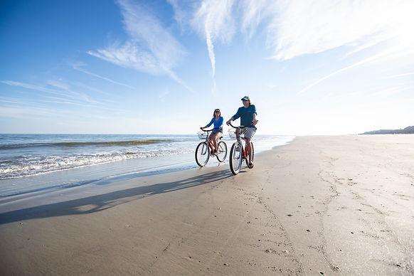 couple riding bikes on beach