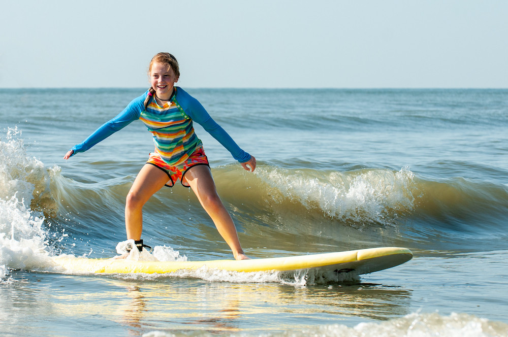 little girl in blue rashguard catching a small wave on surfboard
