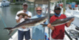 Three Men Holding Fish