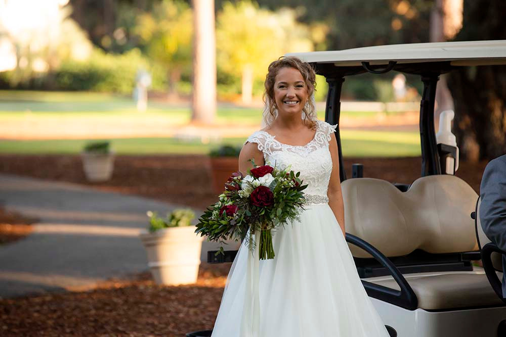 bride with bouquet in front of golf cart