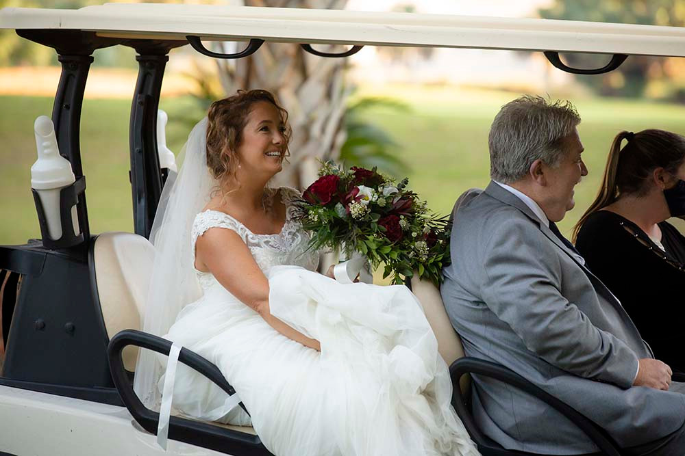 bride and father of bride riding in golf cart