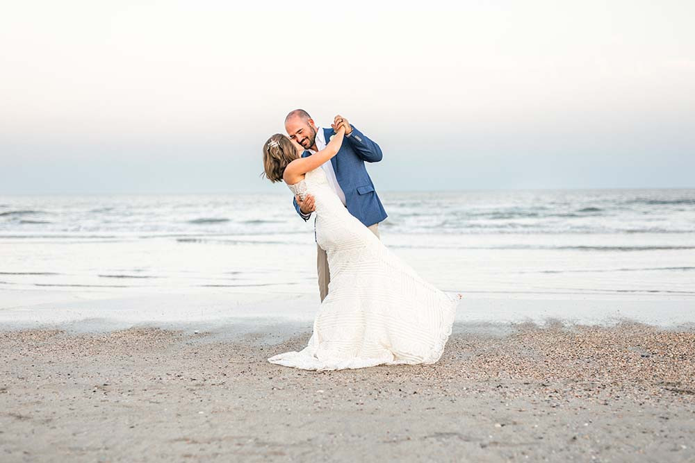 groom dipping bride during a dance on the beach